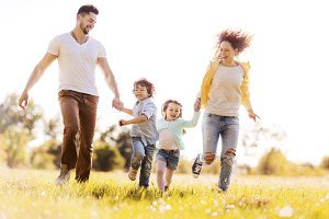 Happy young family running in the park and having fun.
